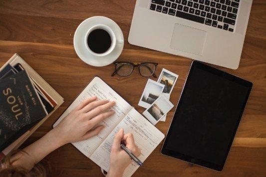 Escritora con café, ordenador, bloc de notas y fotos.