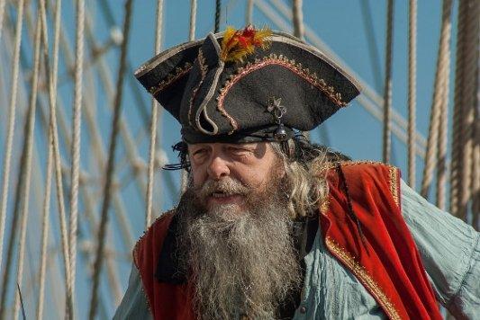Pirata con barba larga y sombrero en un barco.
