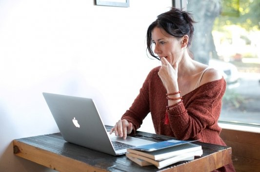 Mujer escribiendo en un ordenador.