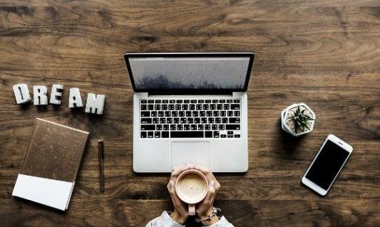 Escritorio con ordenador, cuaderno y café.