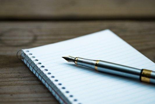 Pluma de metal y un cuaderno en blanco.