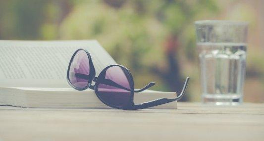 Libro, gafas de sol y un vaso de cristal.