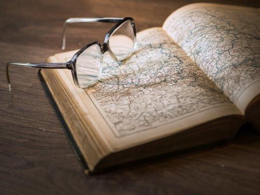 Viejo libro de mapas y unas gafas.