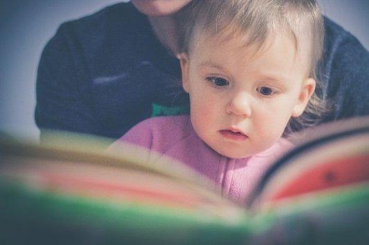 Madre e hija leyendo un libro.