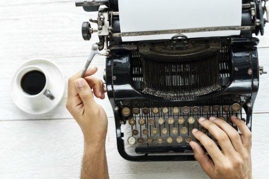 Vieja máquina de escribir y taza de café.