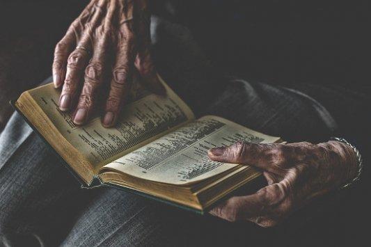 MAnos de anciano sosteniendo un libro.