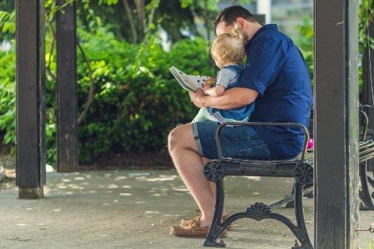 Padre leyendo un cuento a su hijo.