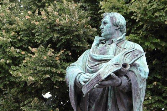 Estatua de un académico renacentista con un libro.