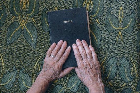 Biblia cristiana con manos ancianas.