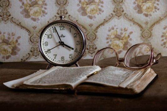 Reloj antiguo con libro y gafas.