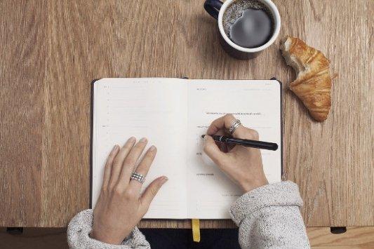 Cuaderno, café y bollo.