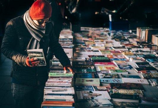 Lector eligiendo libros.