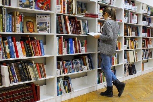 Una lectora frente a una estantería de libros