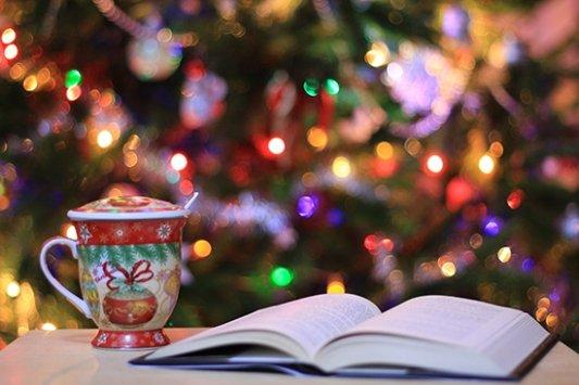 libro y taza frente al árbol de navidad
