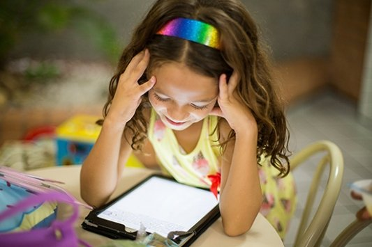 Niña leyendo un libro en una tablet