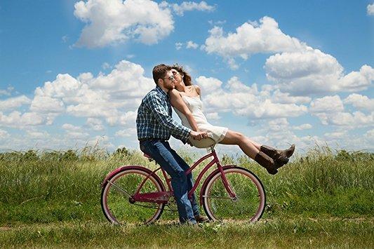 Beso de pareja en bicicleta