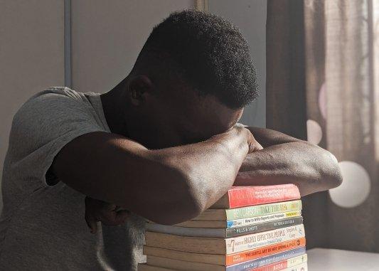Hombre apoyado sobre una pila de libros