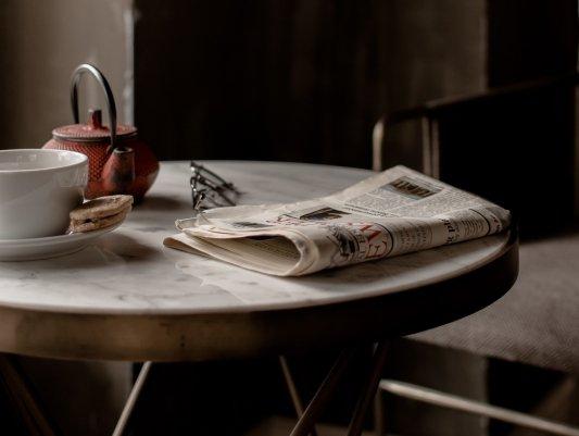 Periódico sobre una mesa junto a un té