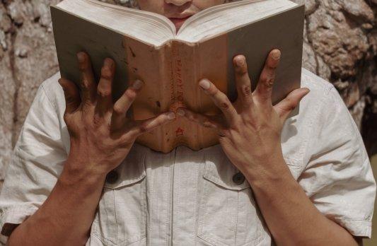 Chico sujetando libro de gran extensión