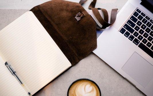 Libreta de anotaciones junto a un café y un portátil