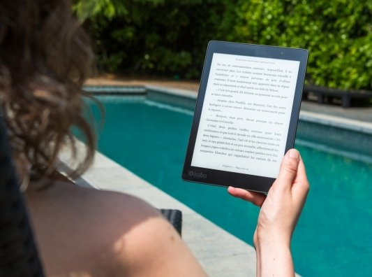 Mujer leyendo ebook en la piscina