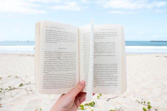 Mano sujetando las páginas de un libro en la playa