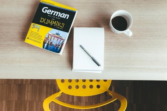 Un libro para aprender alemán, un cuaderno y un café