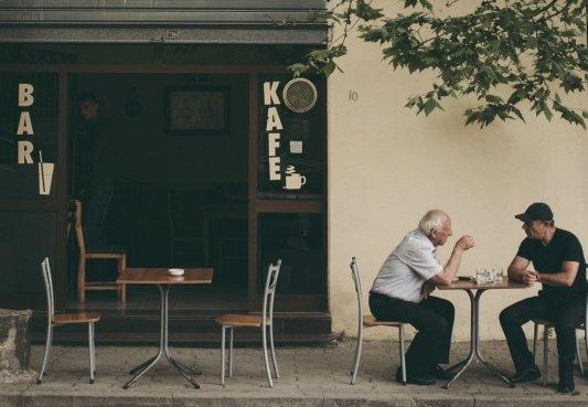 Un anciano y un hombre conversando en la terraza de un bar